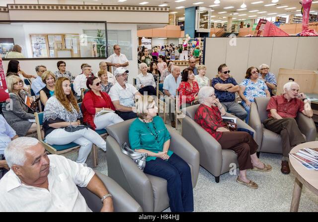 Miami Florida Hialeah JFK Library Health and Literacy Fair interior Hispanic man woman audience listening - Stock Image