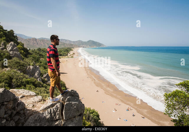Man on top of cliff looking out over Olympos beach, Lycian way, Turkey - Stock Image