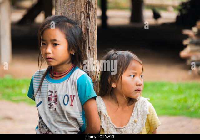 Two shy girls by a post of a hut, Ban Nalan Tai, Khmu Minority Village, Nam Ha National Park, Luang Namtha, Laos - Stock Image