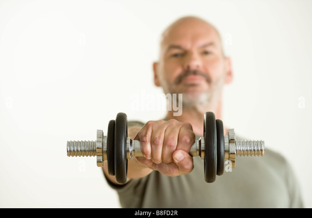Mature lifting dumb bell, Munich, Bavaria, Germany - Stock Image