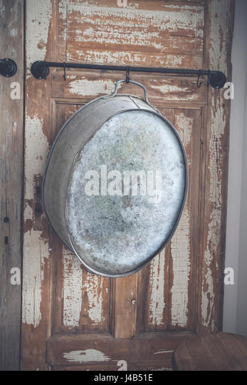 Old stylish iron tub hanging on a wooden wall with grunge paint peeling of the old planks - Stock Image