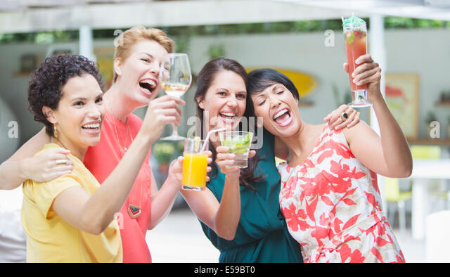 Women cheering together at party - Stock-Bilder