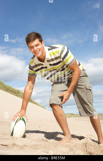 Teenage Boy With Rugby Ball On Beach - Stock Image