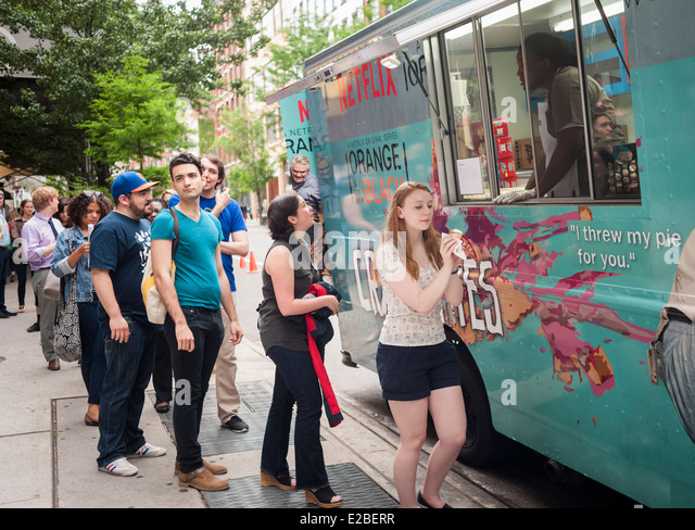 Fans of the Netflix series 'Orange is the New Black' line up at a rebranded food truck in Soho in New York - Stock Image