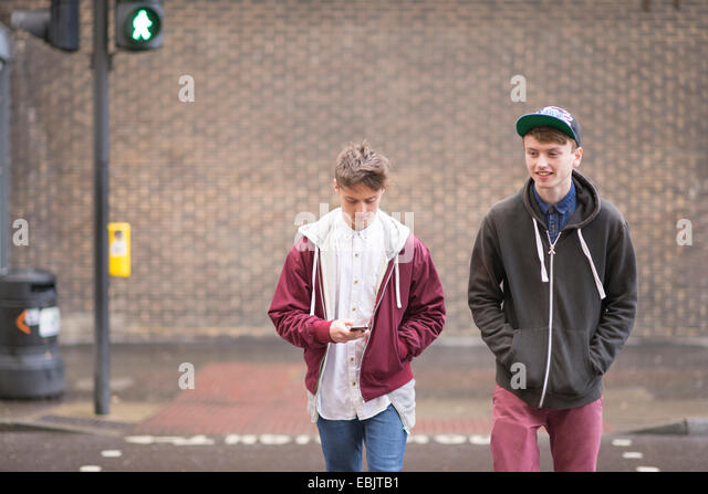Two male friends crossing road - Stock Image