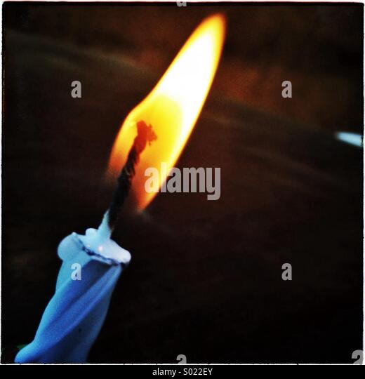 Single flame of a one birthday candle light - Stock Image
