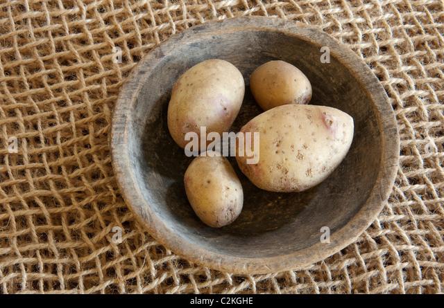 King Edward potato (Solanum tuberosum King Edward). Potatoes a wooden bowl. - Stock Image