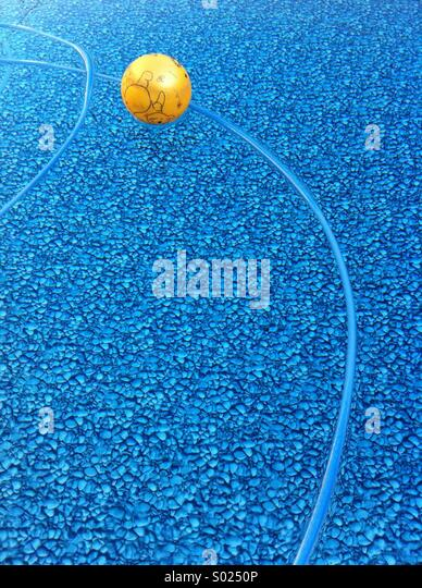 Yellow ball and hose floating in a swimming pool - Stock-Bilder
