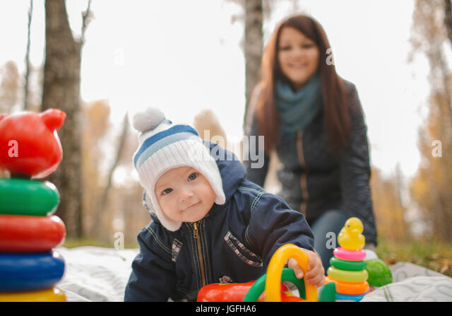 Middle Eastern mother watching baby son playing with toys in park - Stock Image