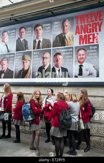 Schoolgirls beneath a theatre poster 'Twelve Angry Men' at the Garrick Theatre, Charing Cross Road, London - Stock Image