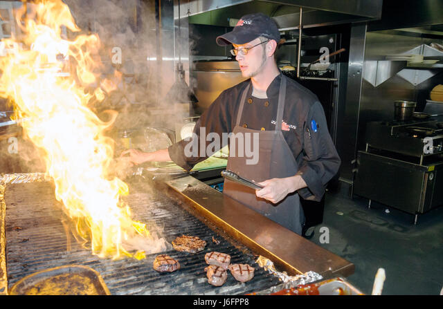 Tennessee Sevierville Kodak Chop House restaurant man cook work flames grill beefsteak food apron fire - Stock Image