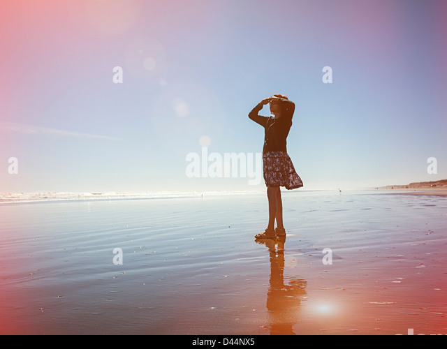 Light leaks, woman looks out to sea, New Zealand. - Stock Image
