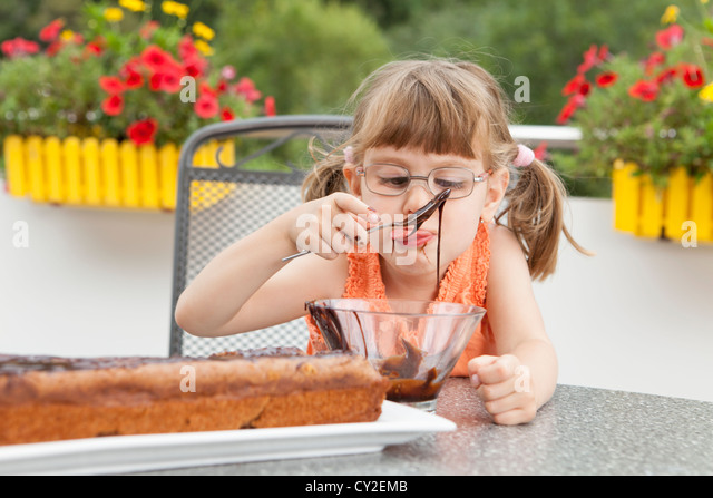Little girl decorating the chocolate cake - Stock Image