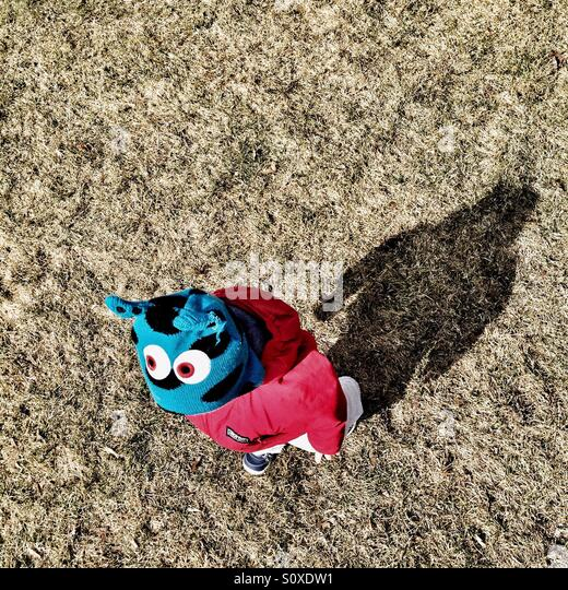 Toddler wearing a monster hat, followed by his shadow. - Stock Image