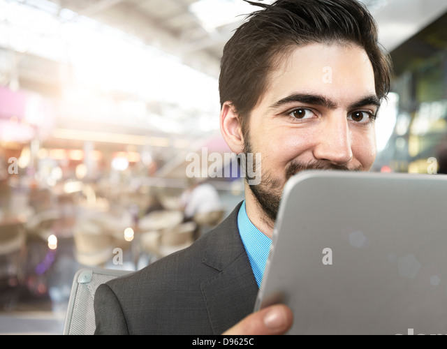 Portrait of young businessman using digital tablet, smiling - Stock Image