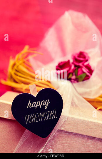 closeup of a gift box ornamented with flowers and tulle, and a heart-shaped black chalkboard with the text happy - Stock Image