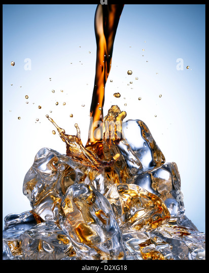 Soda pouring over ice - Stock Image