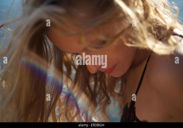 Woman looking down with beam of rainbow light - Stock-Bilder