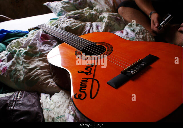 An acoustic guitar with the name Emmy-Lou inscribed sits on a bed - Stock-Bilder