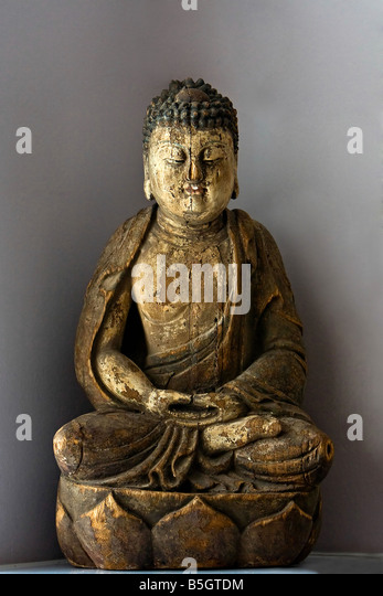 A wooden statue of Buddha sitting in the Lotus position isolated on gray - Stock Image