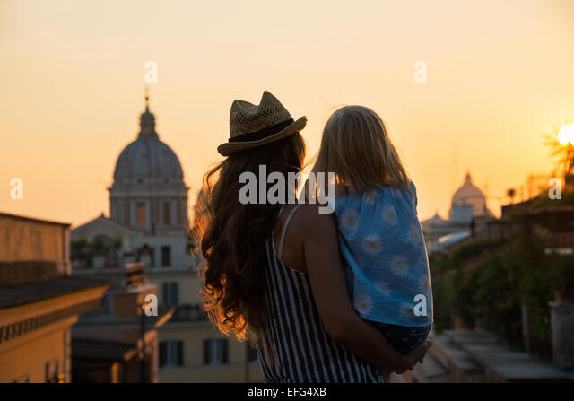 Silhouette of mother and baby girl looking on rooftops of rome on sunset. rear view - Stock Image