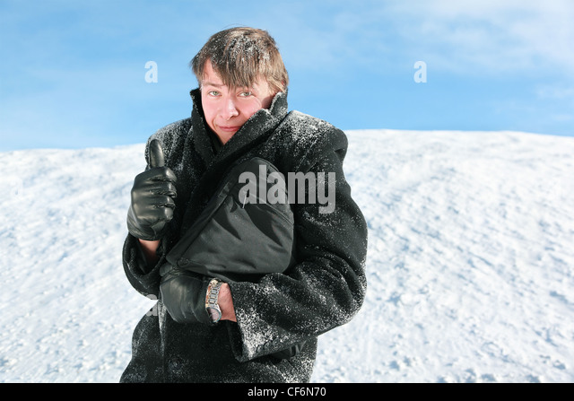 Fellow stands in winter on snow holds  brief-case and shows gesture fingers - Stock Image