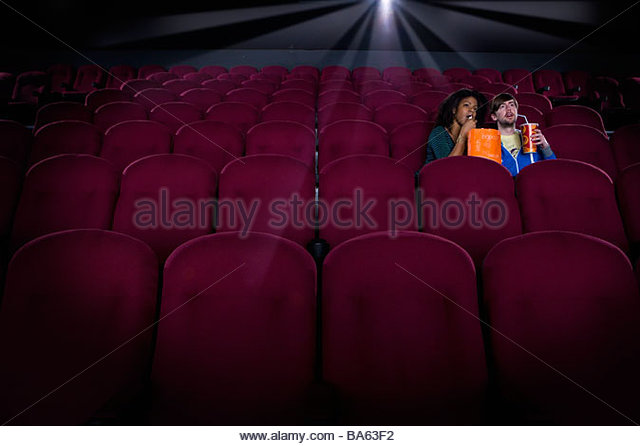 Couple in empty cinema with drink and popcorn - Stock Image