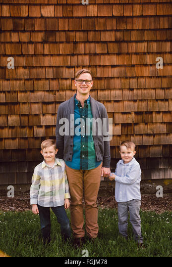 Dad with two kids, both boys, in a lifestyle portrait outdoors. - Stock-Bilder