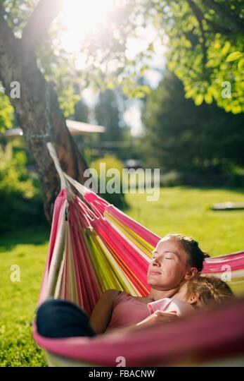 Finland, Heinola, Paijat-Hame, Woman embracing girl (4-5) in hammock - Stock Image