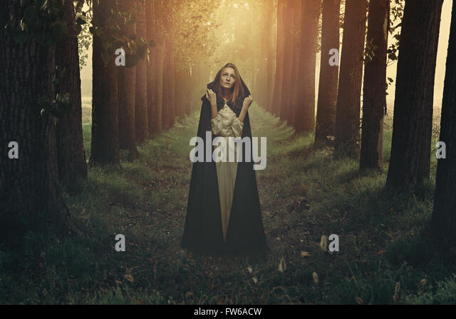 Beautiful woman with black robe in a surreal forest - Stock-Bilder