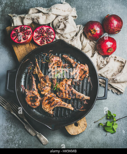 Barbecue dinner. Grilled lamb meat chops with onion and rosemary in black cast iron pan served with fresh pomegranates - Stock Image