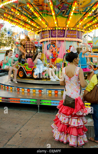 Spanish woman in traditional festive dress waiting next to chlidrens Carousel, merry-go-round at annual fair. Fuengirola, - Stock Image
