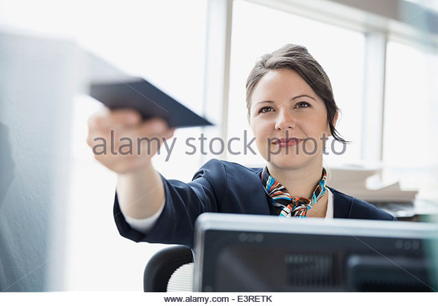 Airport customer service representative holding passport - Stock Image