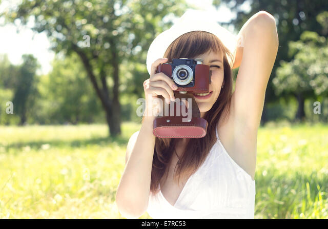 Young pretty woman posing with old film camera in summer park. Girl in White hat photograph with manual camera - Stock Image