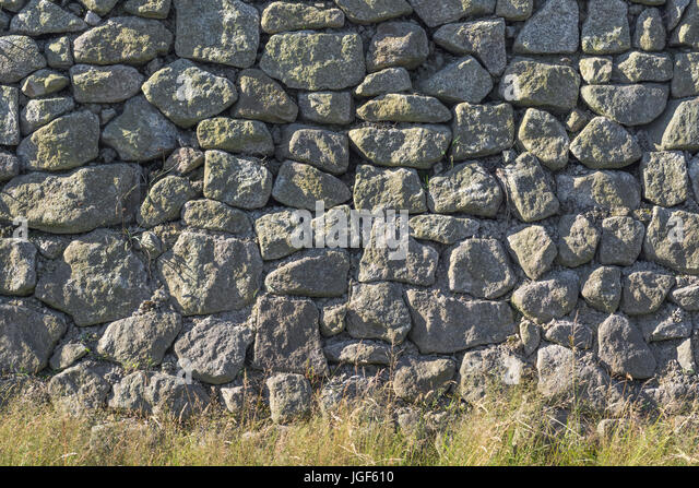 Roadside granite stone wall with grass verge vegetation. - Stock Image