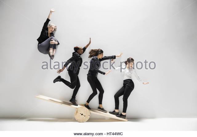 Businesswoman jumping and sliding on seesaw against white background - Stock-Bilder