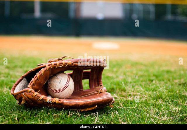 Baseball in glove on field with base and outfield in background. - Stock Image