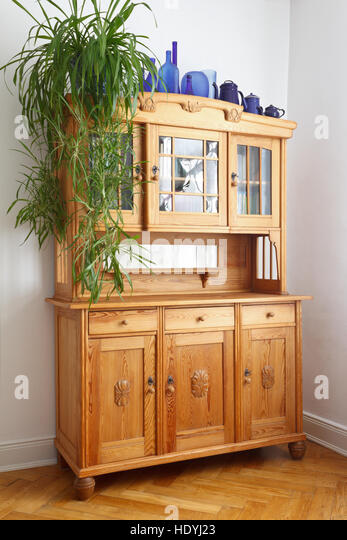 Old pine cupboard with wooden and glass doors, drawers, on oak herringbone parquet flooring, nostalgic furniture - Stock Image
