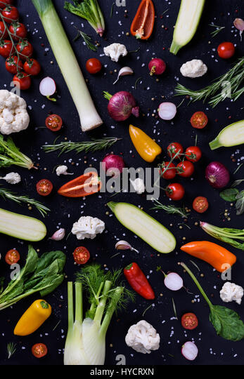 Cooking and seasoning ingredients over black. Colorful vegetables over wooden background. Healthy diet concept. - Stock Image