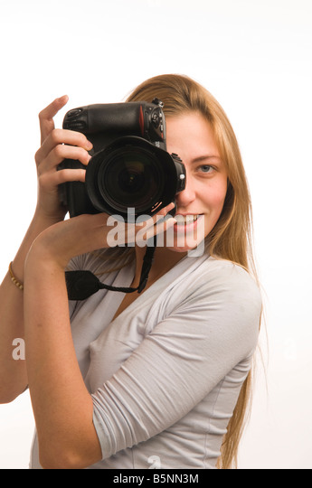 A Young blonde woman photographer using an expensive Nikon digital SLR DSLR camera taking photographs in studio - Stock Image