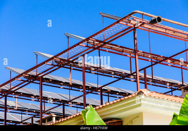 Solar panels on a metal frame on the roof of a building in a hot climate - Stock Image