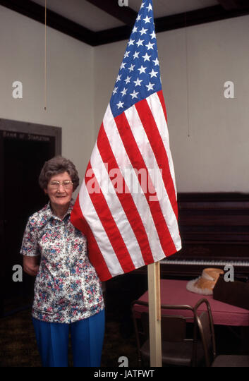 Elderly woman standing beside an American Flag - Stock Image