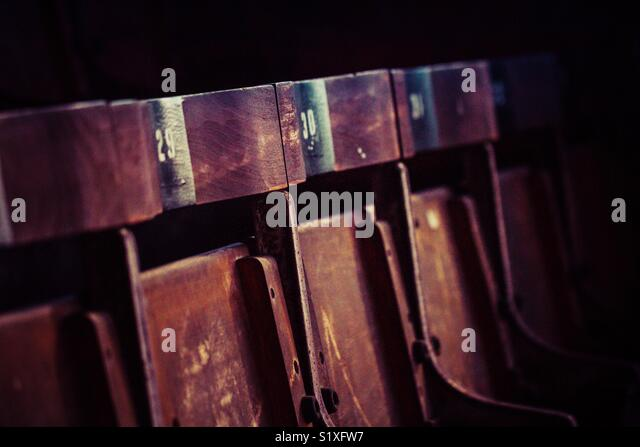 A row of hard wooden seats with numbers on at an empty football stadium at night - Stock Image