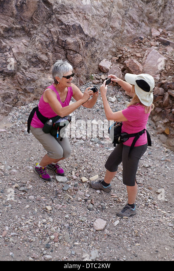 Two senior female hikers photographing each other - Stock Image