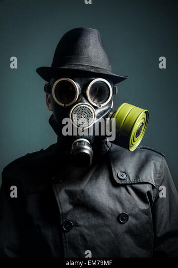 Man in gas mask, raincoat and black hat at dark background - Stock Image