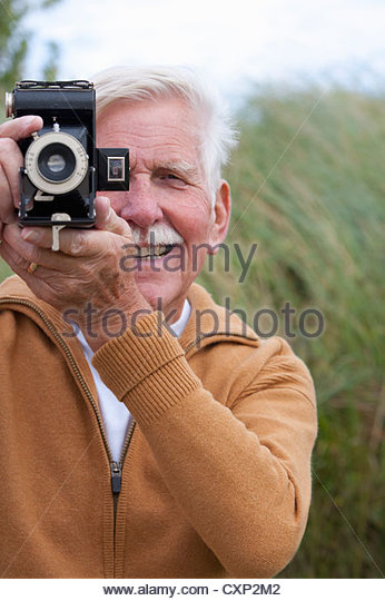 Portrait Of Senior Man With Old Fashioned Camera In Sand Dunes - Stock Image