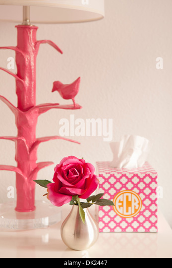 Pink lamp, rose and monogrammed tissue box on nightstand - Stock Image
