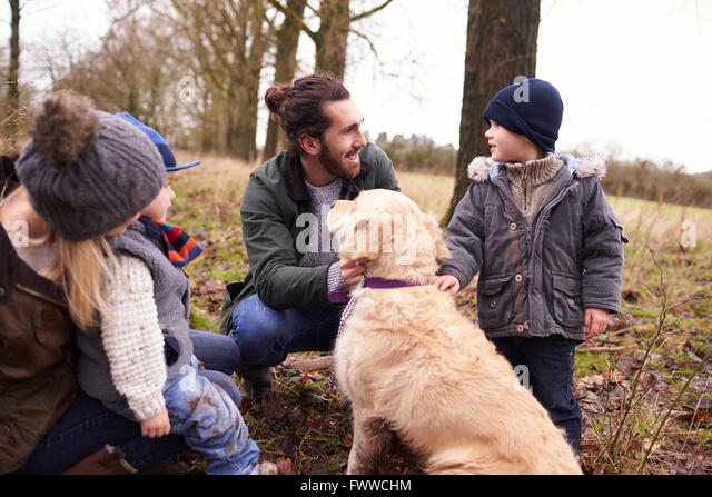Family With Dog On Winter Walk Playing In Countryside - Stock-Bilder