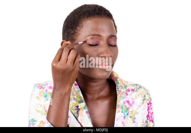 Young african woman doing her makeup isolated on white background - Stock Image