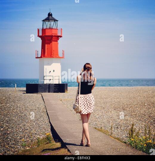 Woman photographing lighthouse, Isle of Man, England UK - Stock Image